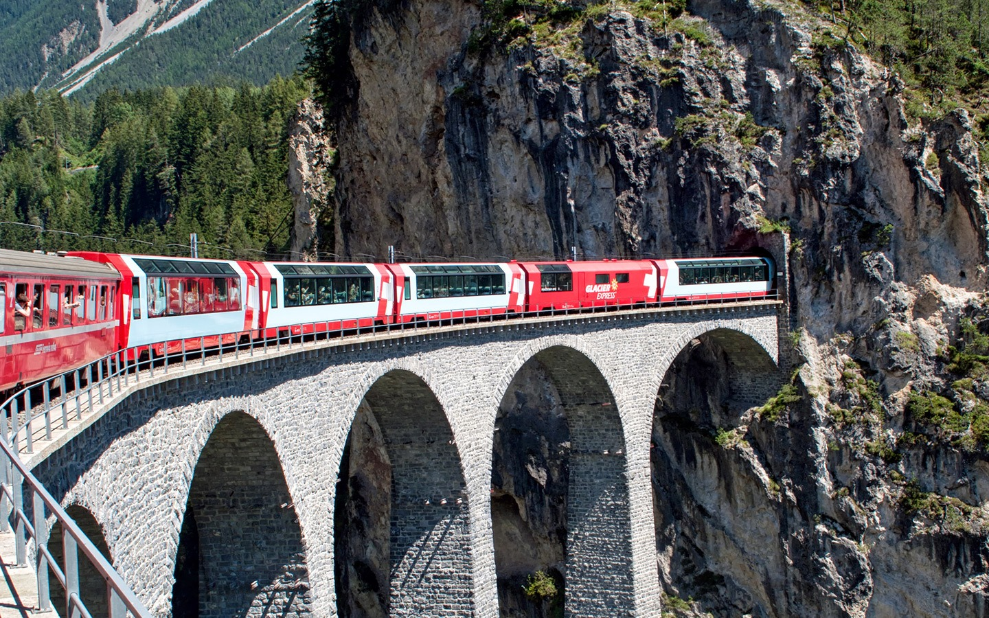 Glacier Express scenic train crossing the Landwasser Viaduct in Switzerland