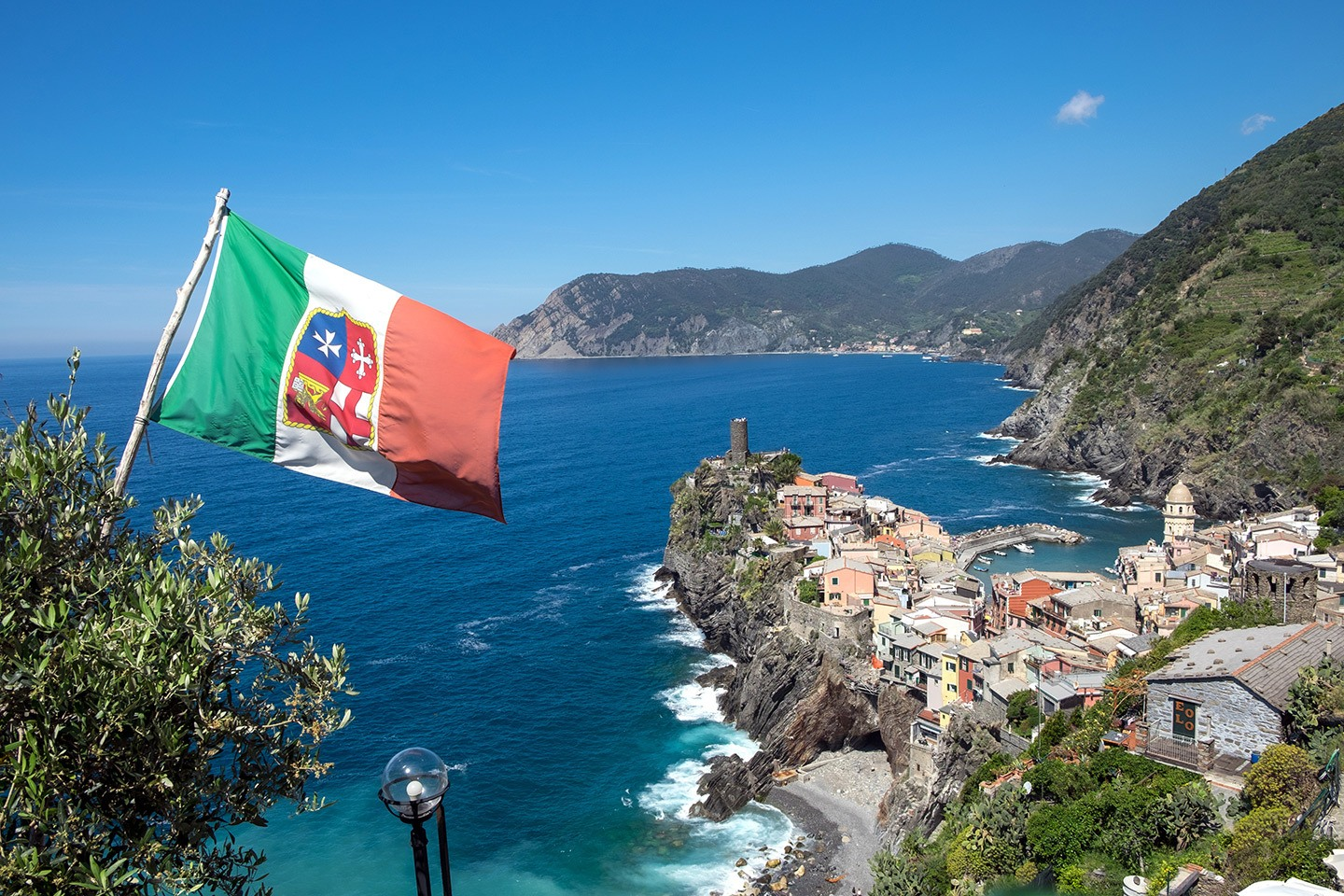 Beautiful Vernazza from the cliff path with a flag blowing in the wind