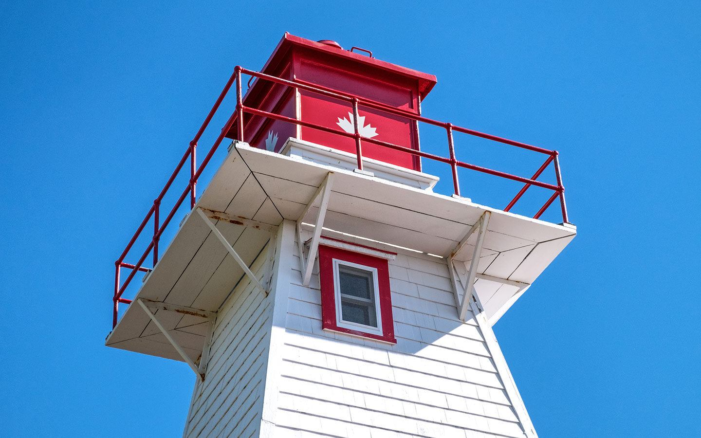 Red and white lighthouse against a blue sky in PEI, Canada