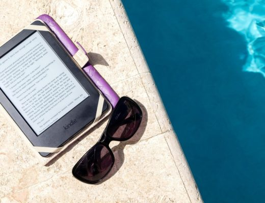 Kindle and sunglasses by the pool